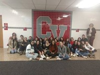 students in front of c v mural