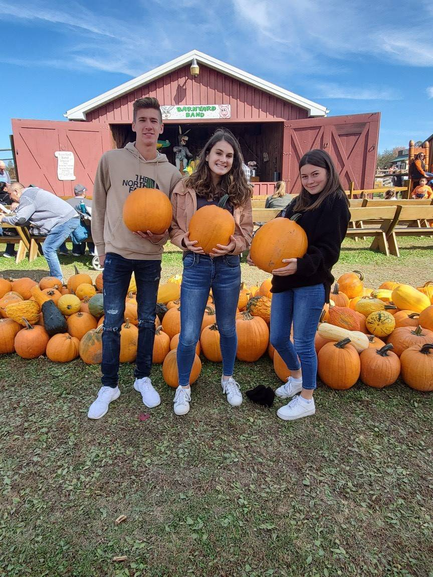 Chenango Valley French Exchange students holding pumpkins
