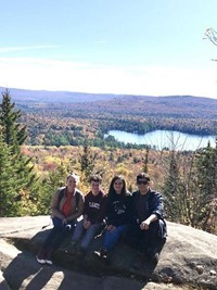 students sitting on rock on top of mountain