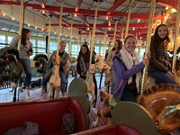 students riding carousel