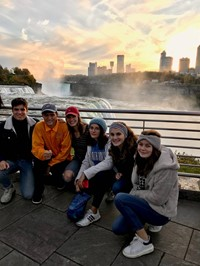 students sitting next to niagra falls