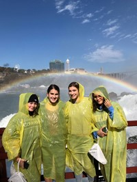 students standing next to rainbow at niagra falls