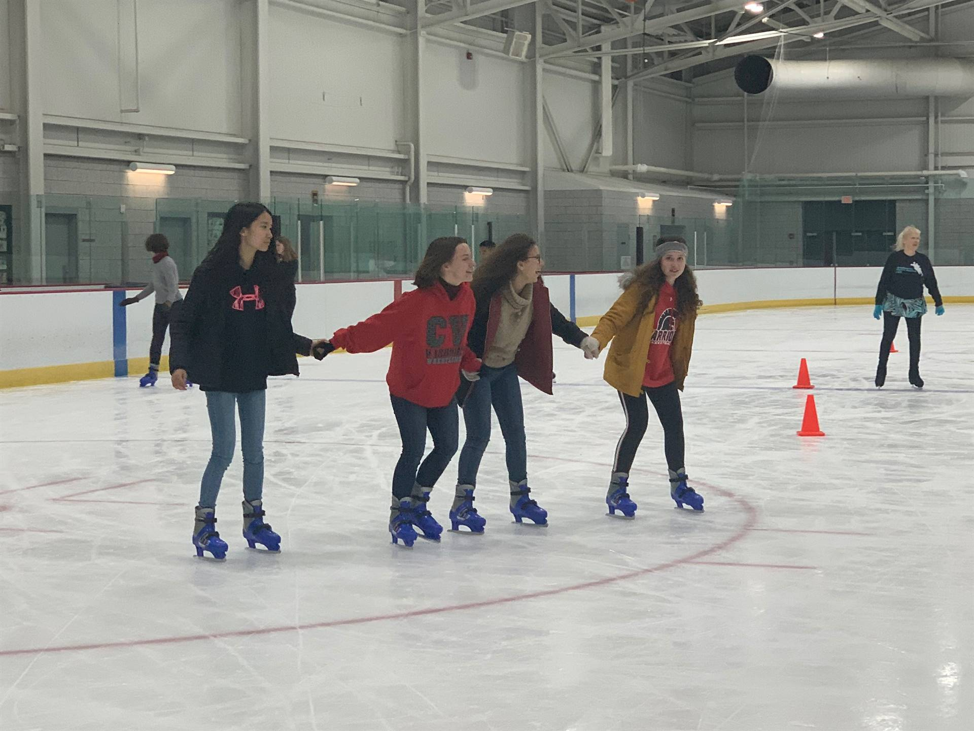 students holding hands ice skating