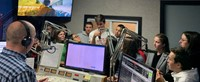 wide shot of students talking to radio station host
