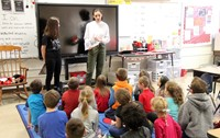 french students reading to elementary class