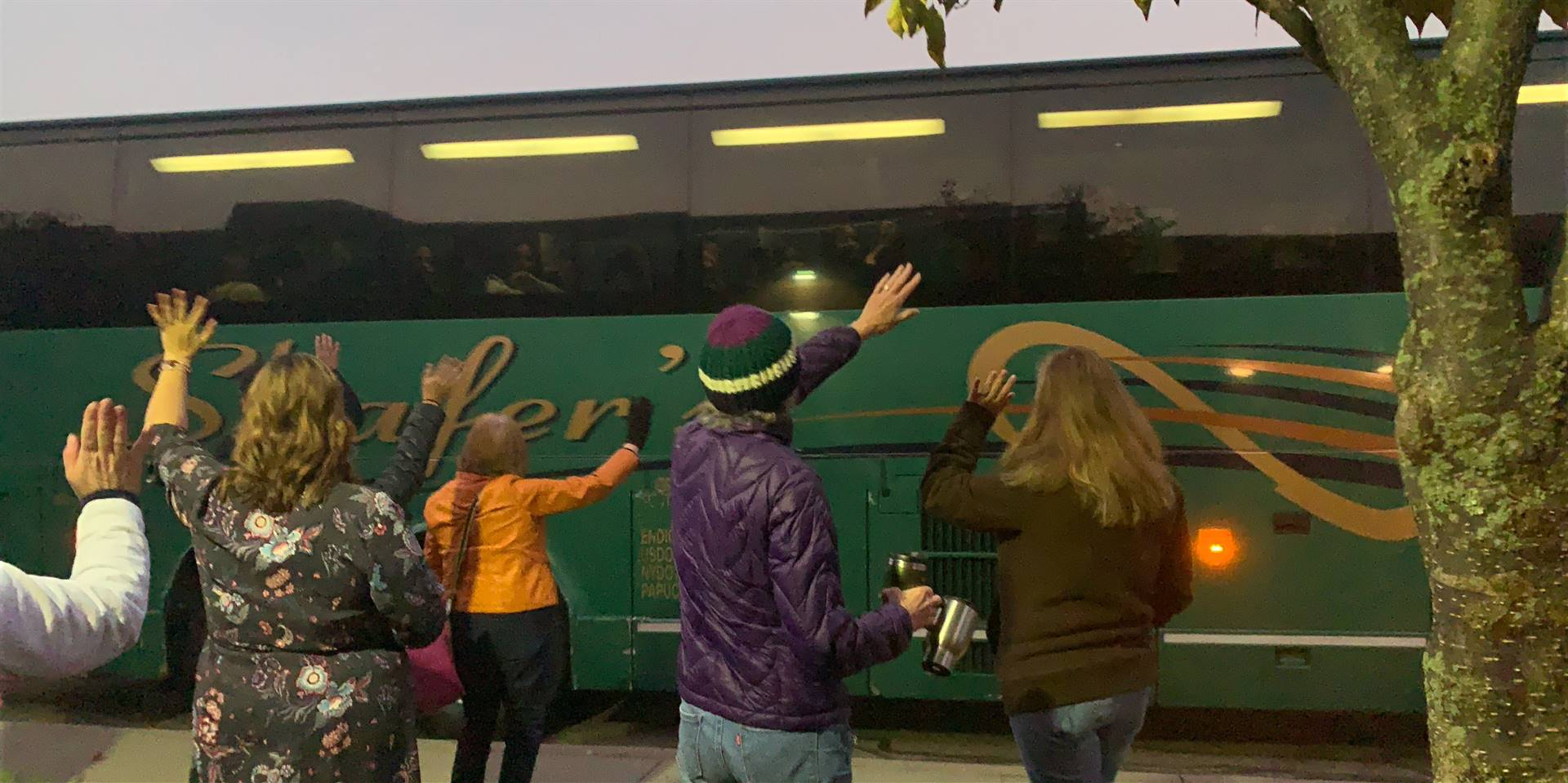 people waving to bus