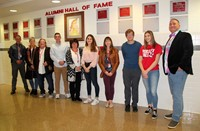 honorees and student tour guides standing in front of alumni hall of fame wall