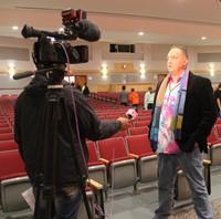 honoree adam cornell speaking to news reporter
