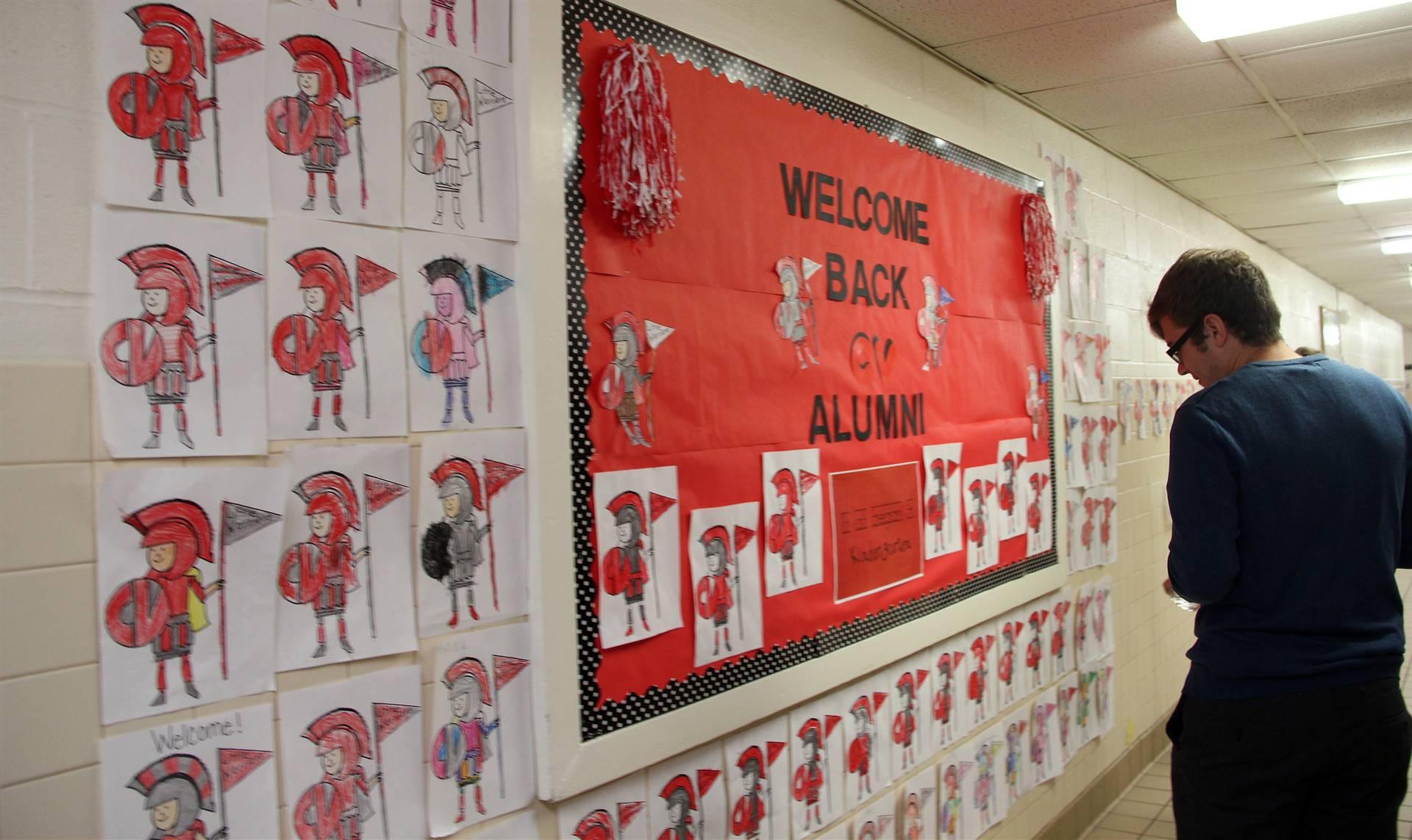 student looking at wall welcoming alumni