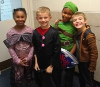 four students in costumes