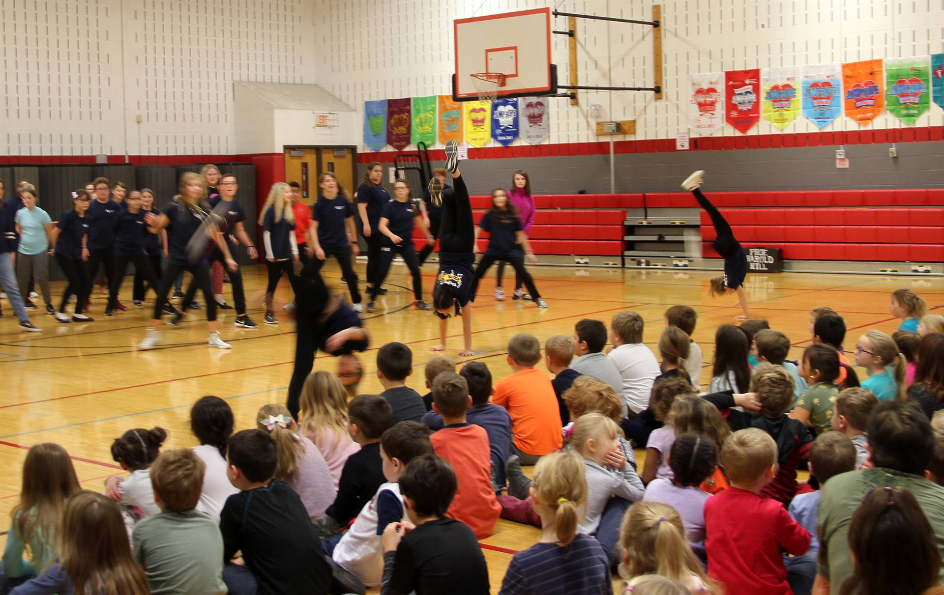 middle school students doing flips during performance