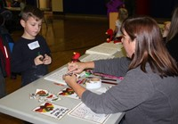 student and adult at activity station