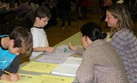 two students and two adults at activity station