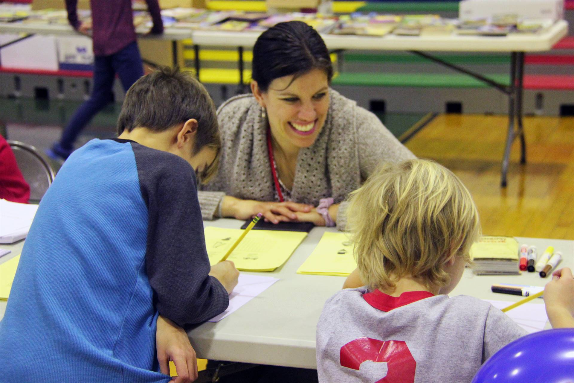 two students and adult at activity station
