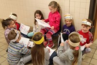 first grade student reading to peers