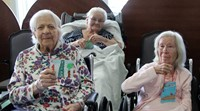 residents holding up ornaments smiling