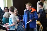 wide shot of chorus performing for residents