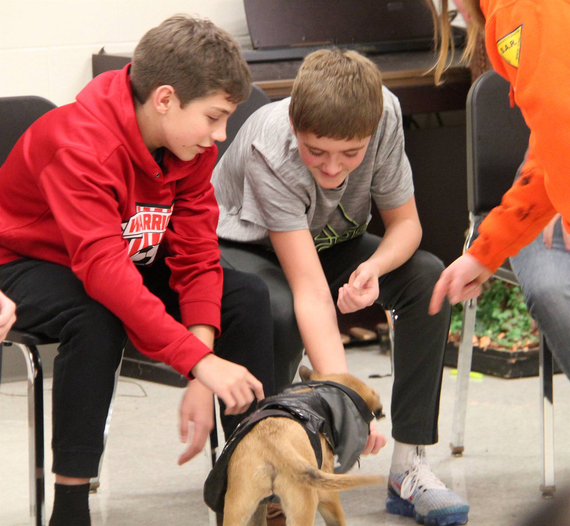 two students petting puppy