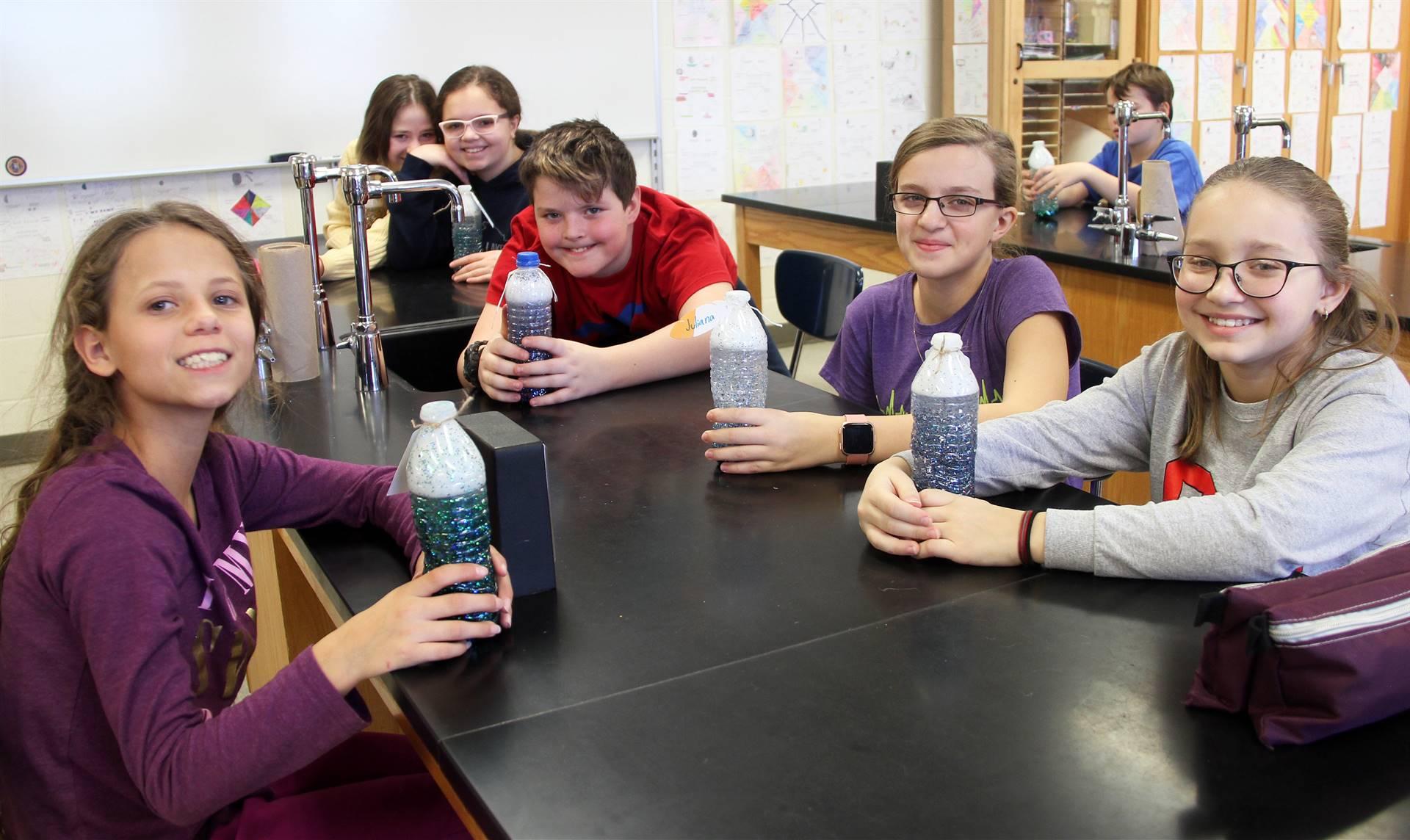 students smiling holding mindfulness jars