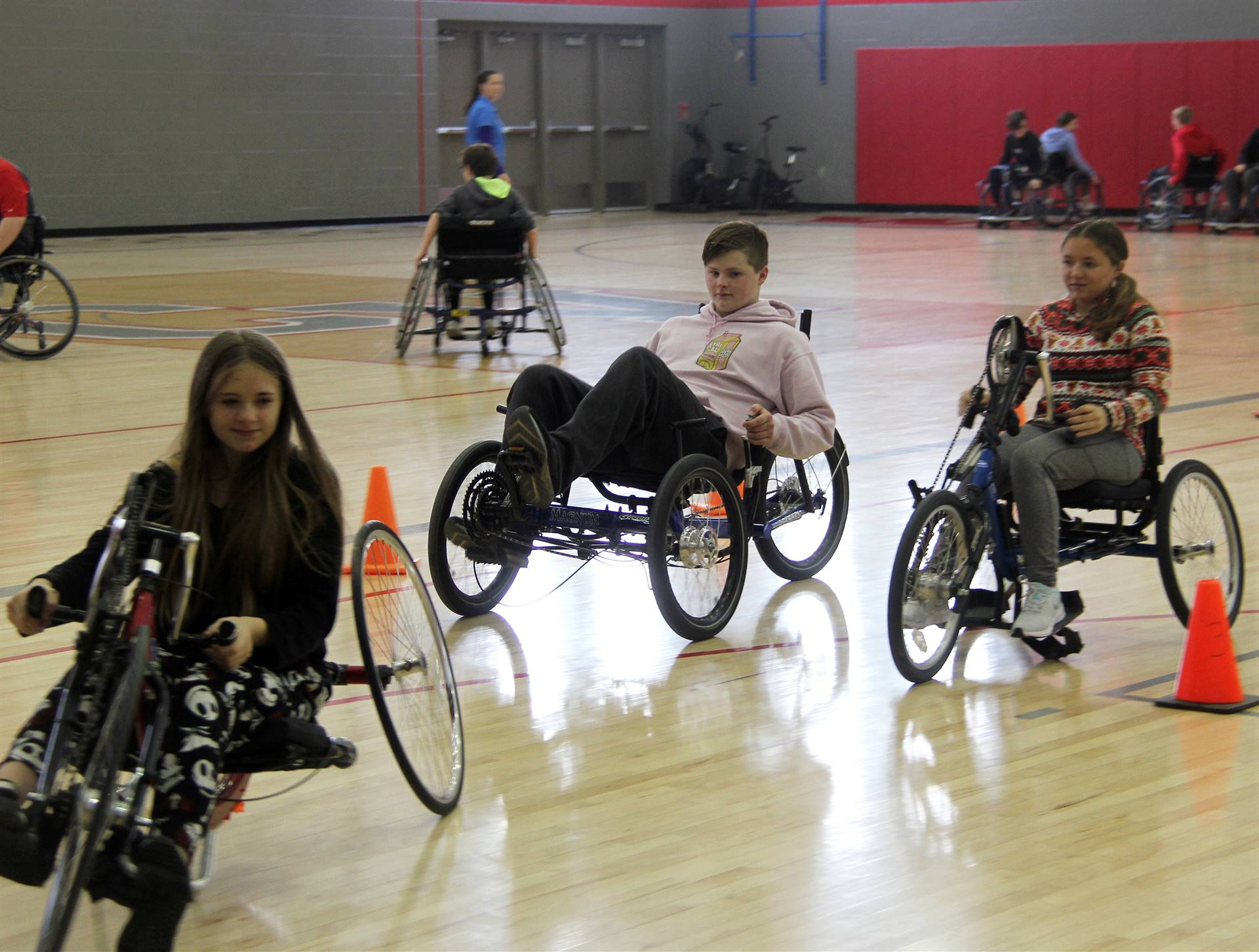 medium shot of students taking part in adaptive sports in gymnasium