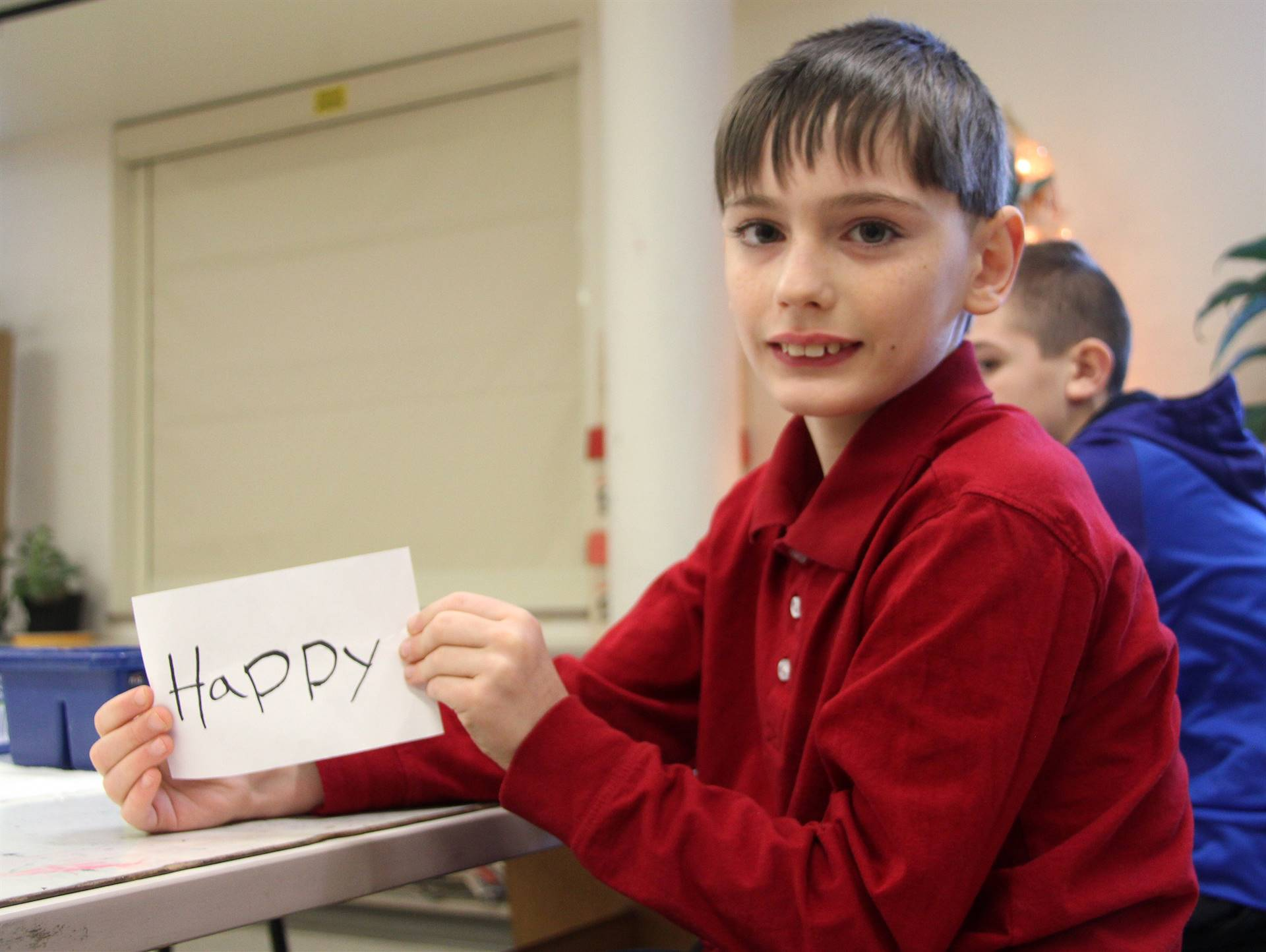 student holding up art project that says happy