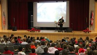 wide shot of jared campbell performing for students