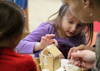 student decorating gingerbread house