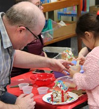 people decorating gingerbread house
