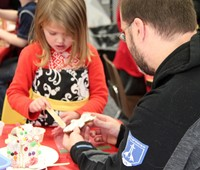 two people making gingerbread house