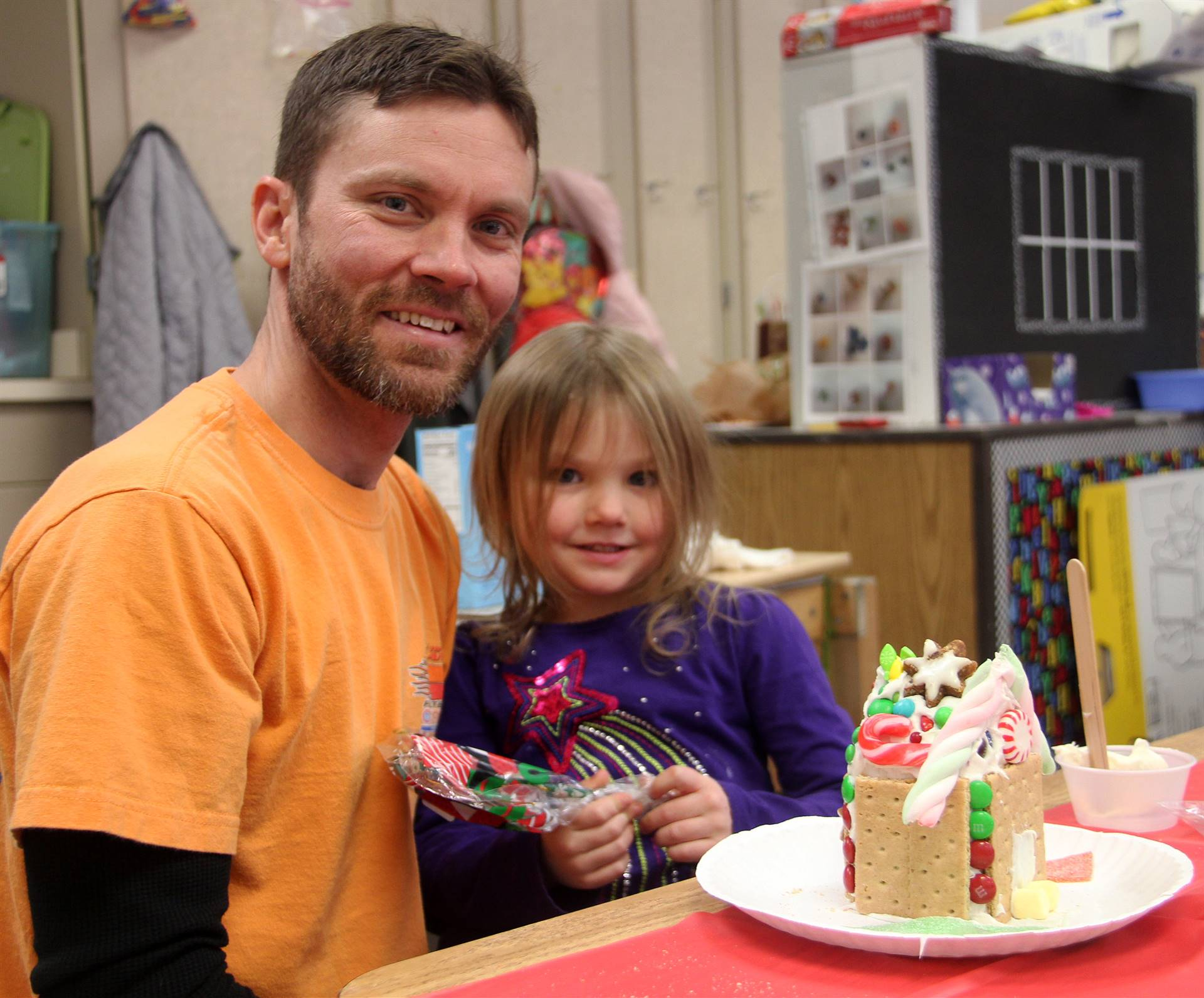 two people smiling next to gingerbread house