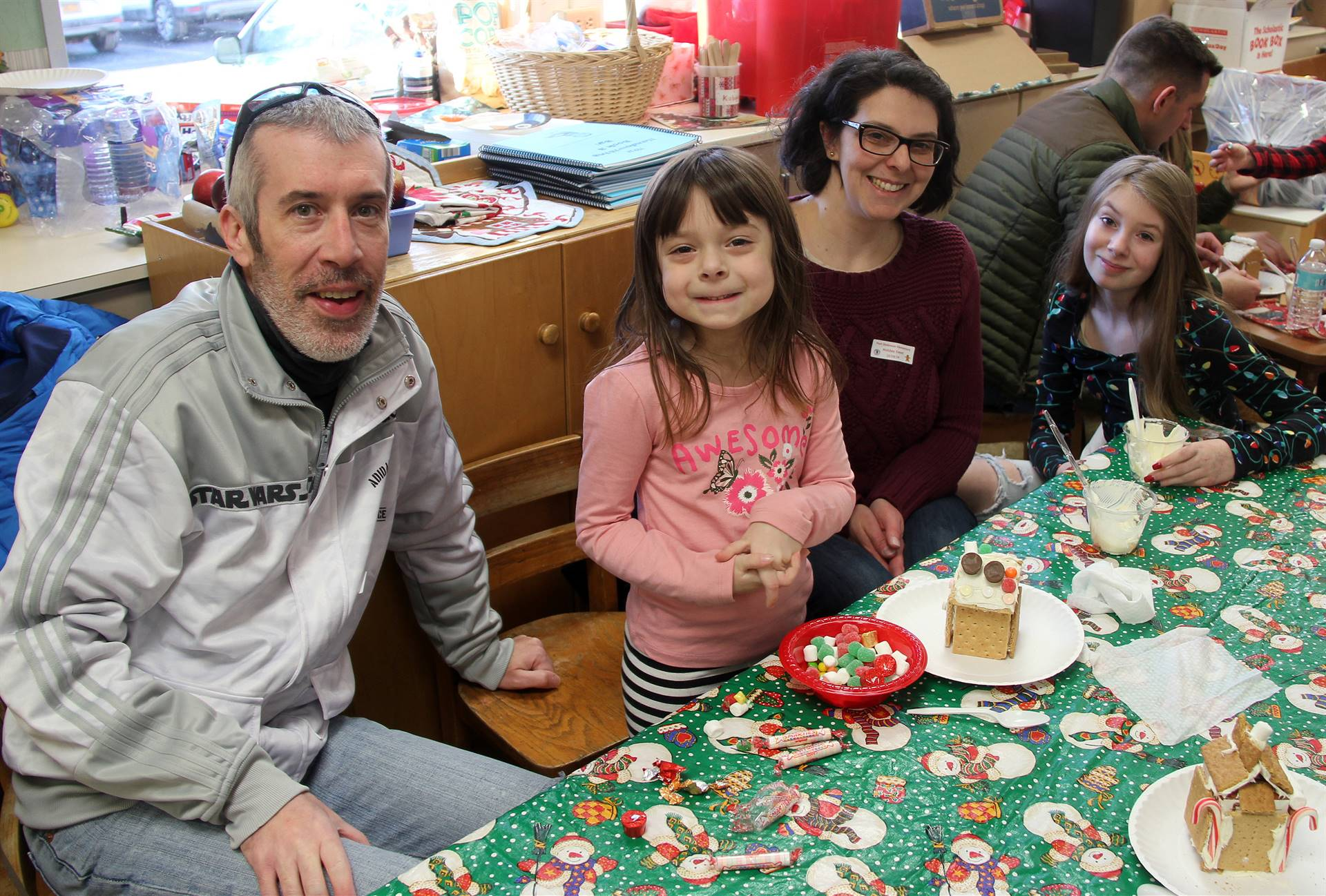 four people smiling next to gingerbread house