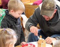 two people working on gingerbread house