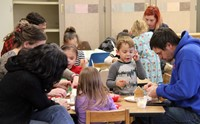 families working on gingerbread houses