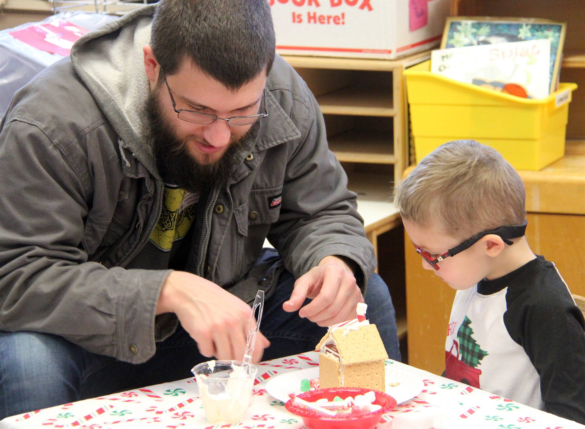 two people creating gingerbread house