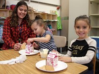 three people smiling next to gingerbread houses