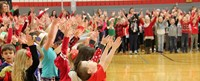 students singing with hands in the air