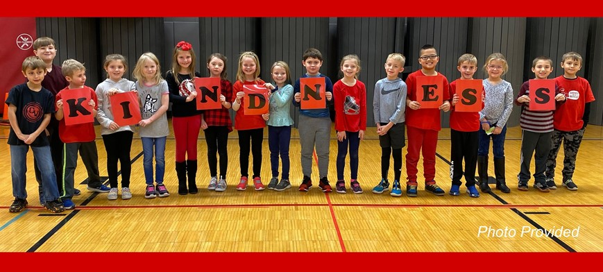 students holding up letters that spell out kindness