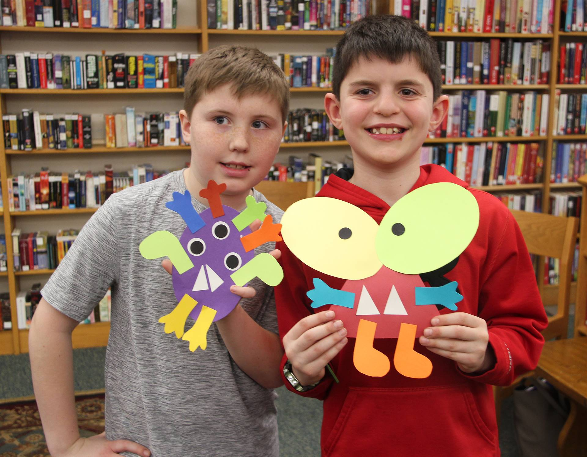 two children holding monster crafts they created