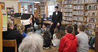 wide shot of theatre guild member reading book to library guests