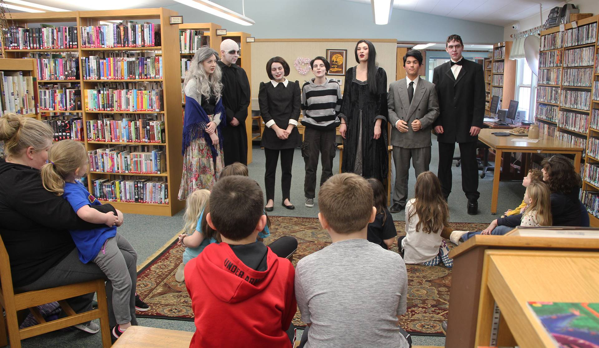 wide shot of theatre guild members speaking in front of library guests