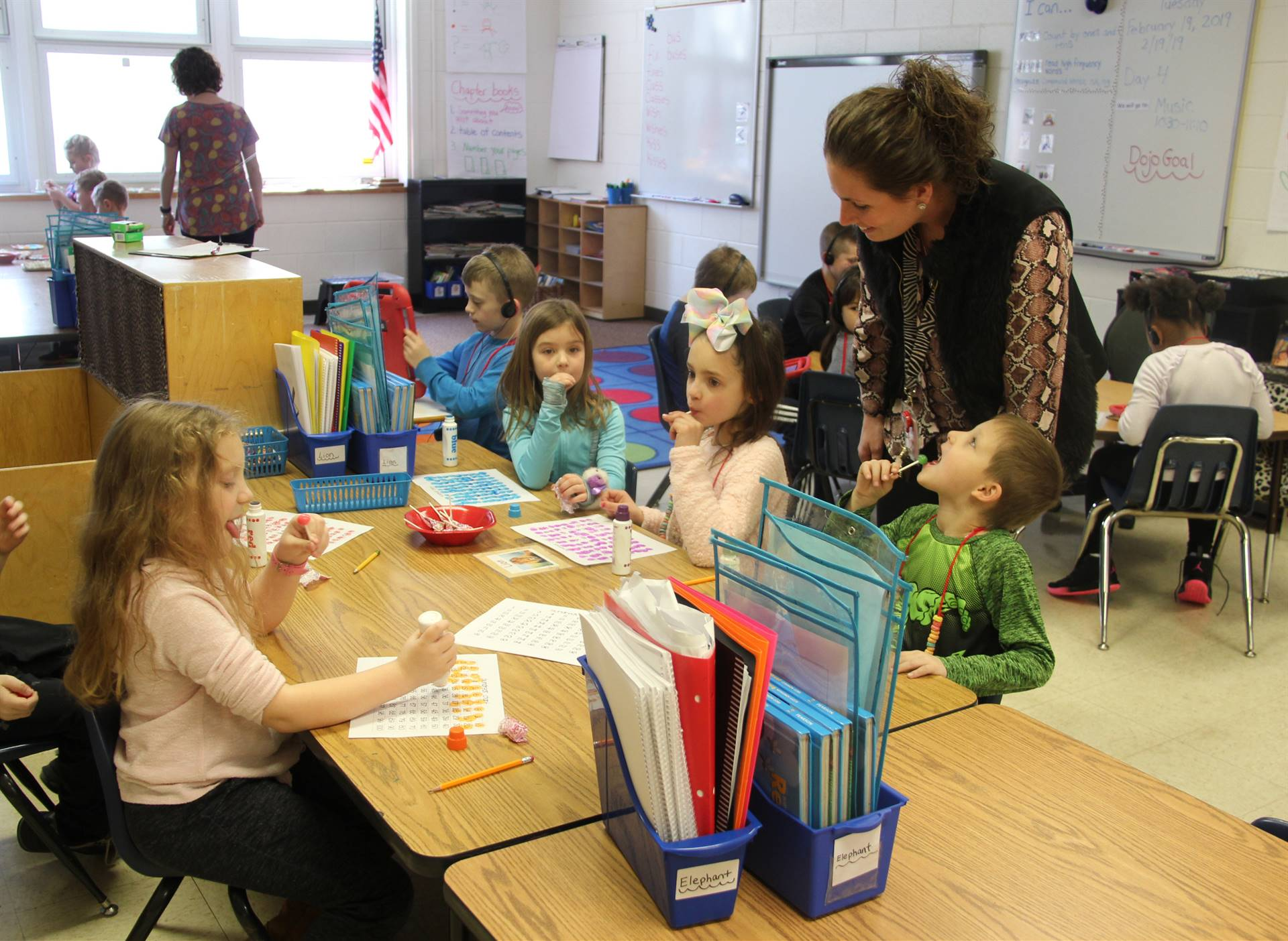 students and teacher working on 100 days of school activity in classroom