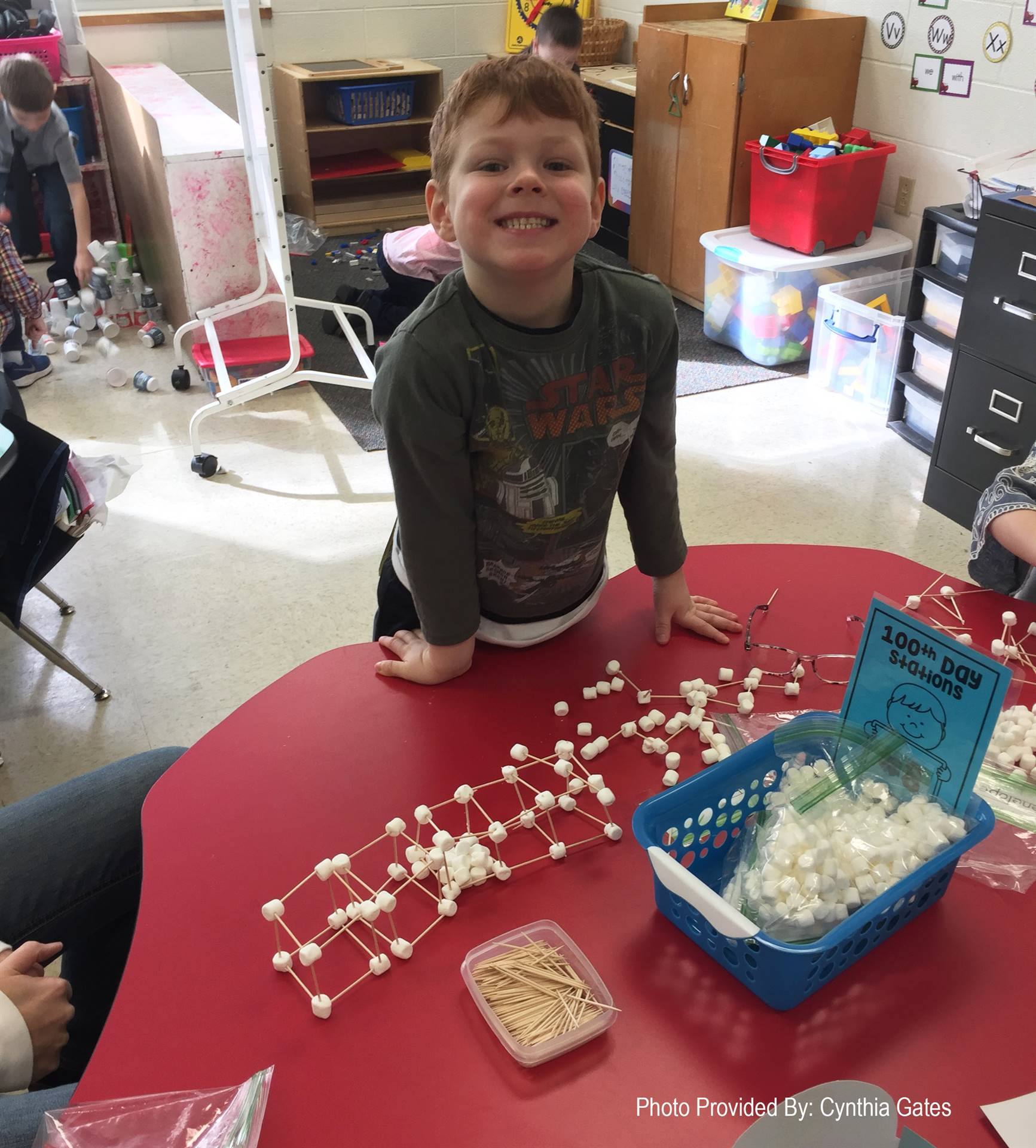 student smiling next to 100 days of school activity