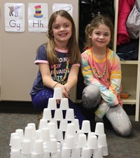 students sitting next to tower made from 100 cups
