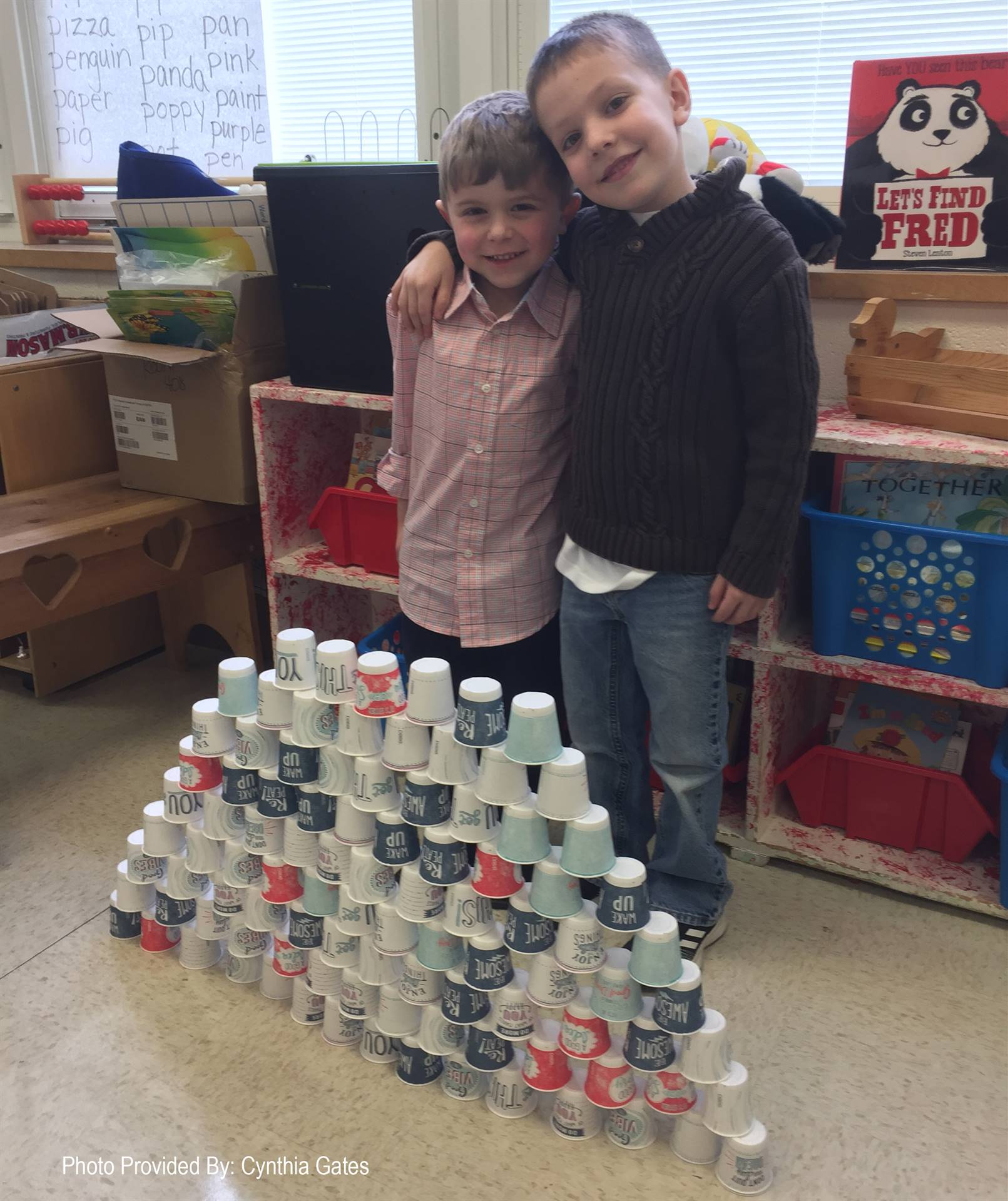 students standing next to tower made from 100 cups