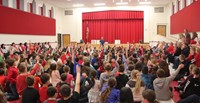 wide shot of auditorium with students raising their hands