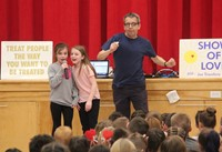 students singing into microphone at assembly