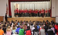 medium shot of high school students performing in front of chenango bridge elementary students