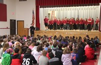 wide shot of mister vanderslice speaking to chenango bridge elementary students with high school stu