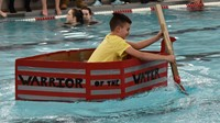 student competing in cardboard boat races