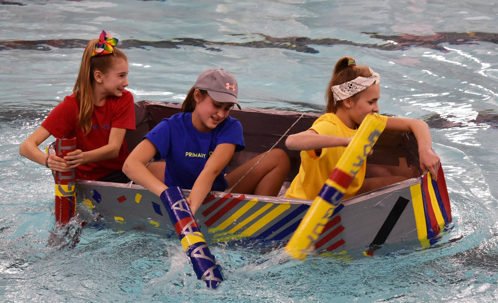 three students competing in cardboard boat races